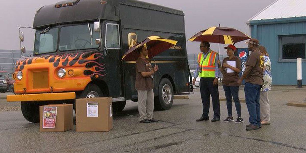 UPS employees stuff school bus with supplies for students