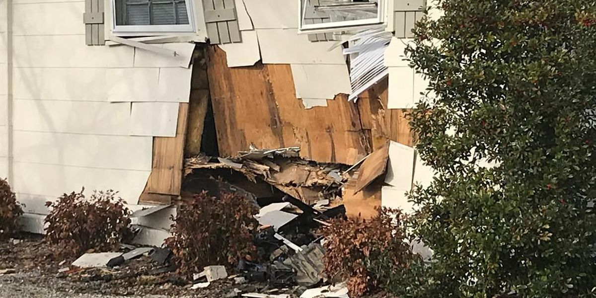 Vehicle hits home, sends debris on top of woman