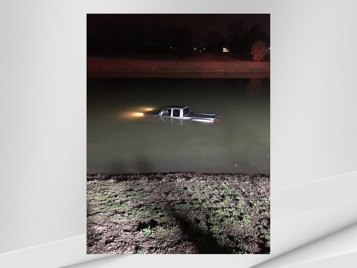 Crews rescuing driver, truck stuck in pond in south Louisville