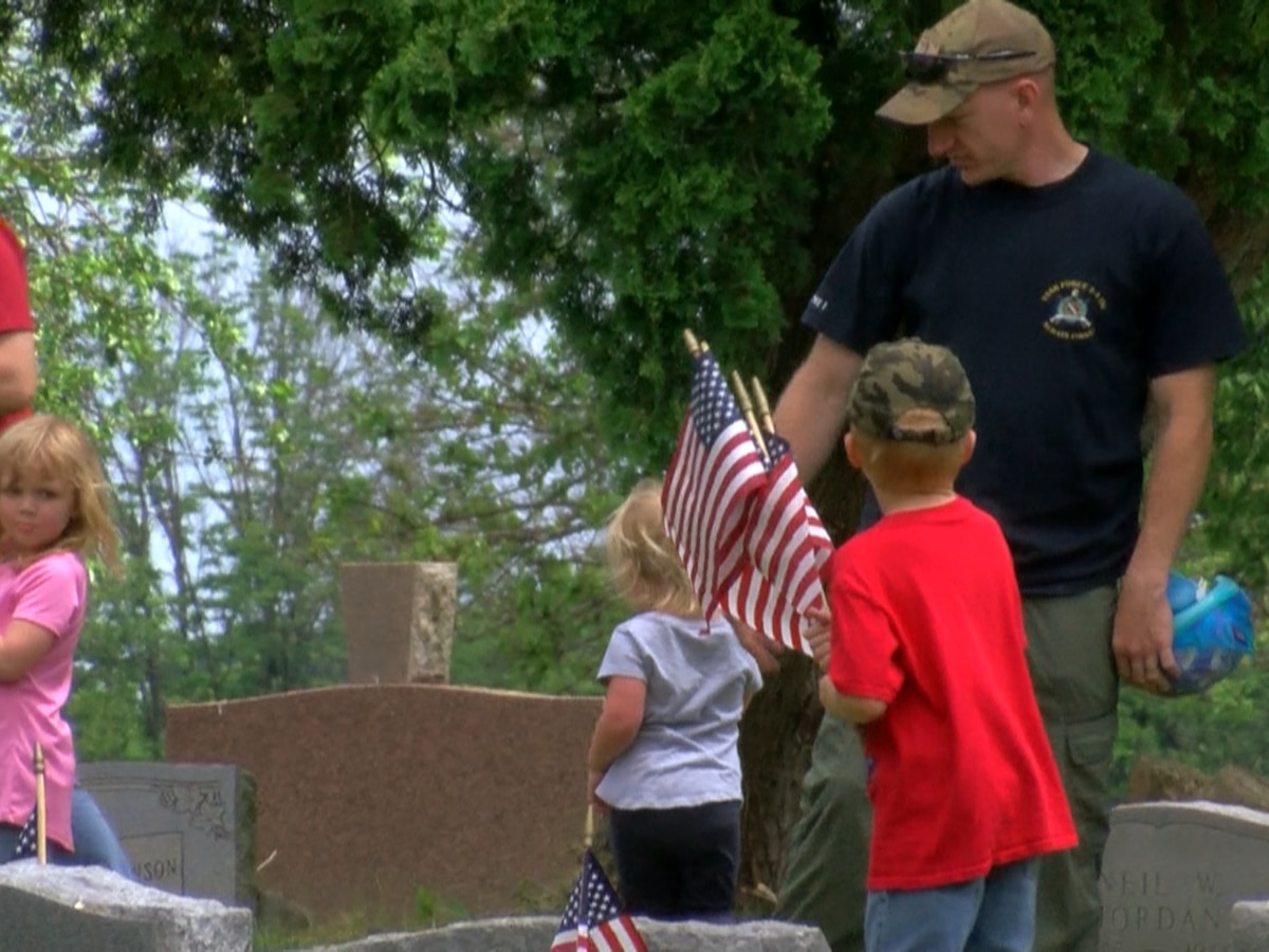 Volunteers stake flags on veterans' headstones memorializing those laid to rest